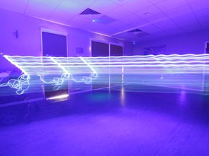 A room that is coloured with blue light with lines of light drawn across the space