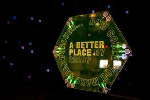 A suspended illuminated yellow hexagon etched with the words 'How could you make Scarborough a better place by 2029?' and suspended in a dark space with starlight in the background