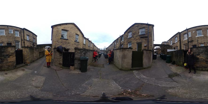 A distorted photograph of alleyways behind stone terrace houses. Four people face each other in pairs down the middle alley whilst one person in each of the other alleyways looks on