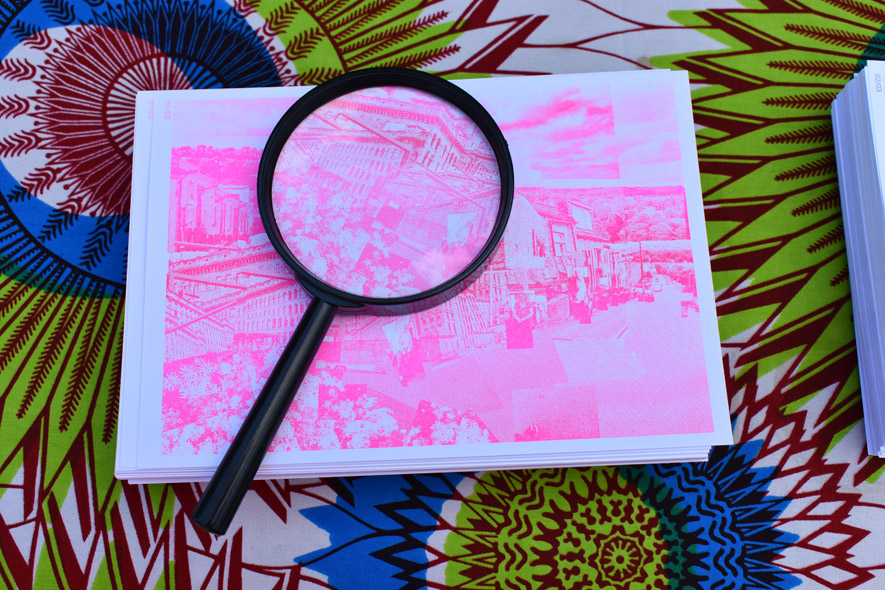 A magnifying glass sits on top of a stack of fluorescent pink printed cards on a brightly coloured tablecloth