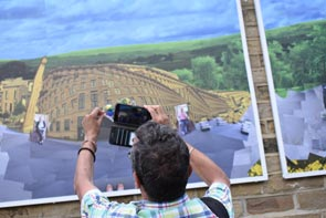 A person photographs a large artwork on an outdoor wall