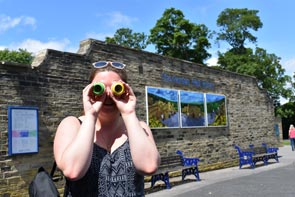 A person holds a pair of kaleidoscopes up to their eyes whilst standing in front of a large photographic artwork on an outdoor wall