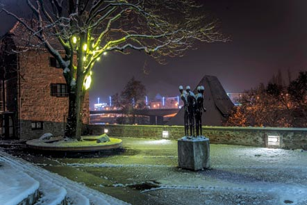 A snowy square at night, overlooking a large river, a sculpture of standing figures is in the foreground and to the left there is a snow covered tree suspended with large etched illuminated hexagons