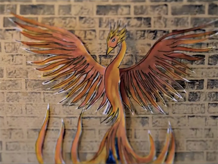 Animation still: a drawing of a phoenix on a brick wall background